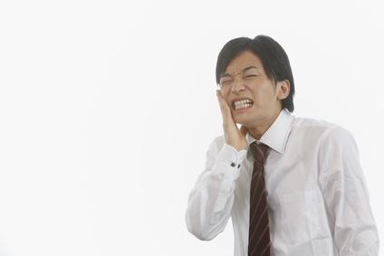 歯痛で苦しむ若い男性